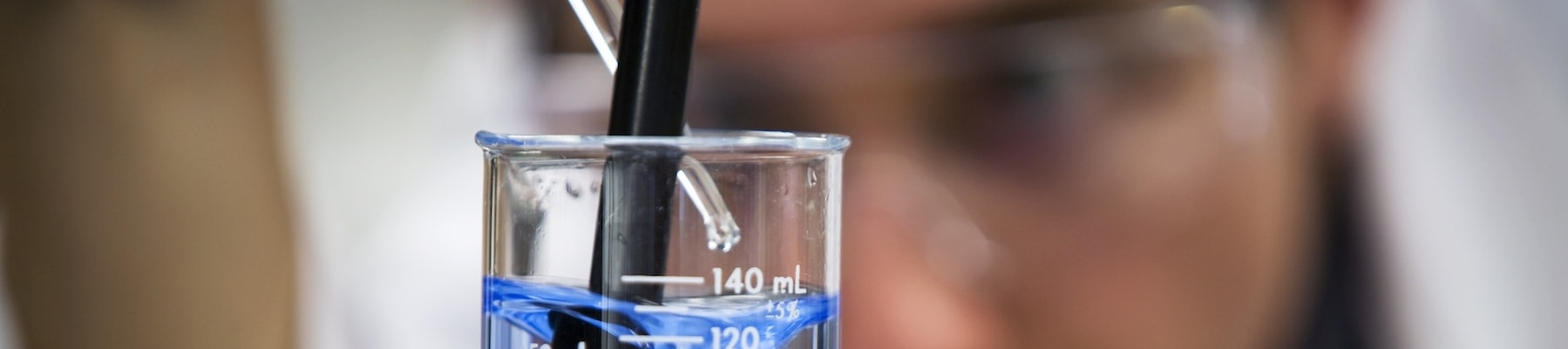 Chemist-in-Lab-Focus-on-Beaker-Close-Up-000008476990_Full-min